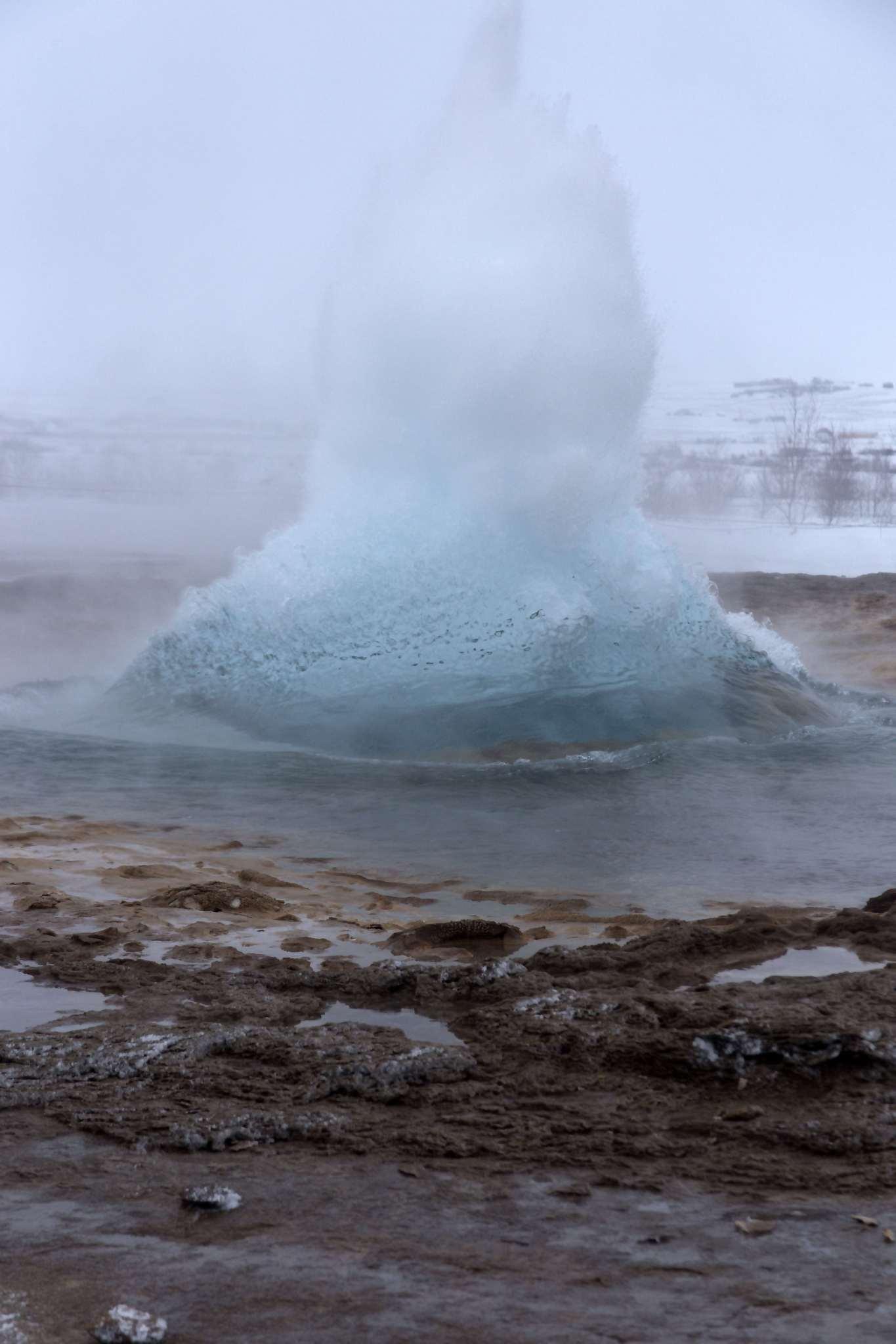 A geyser at Geysìr starts to blow