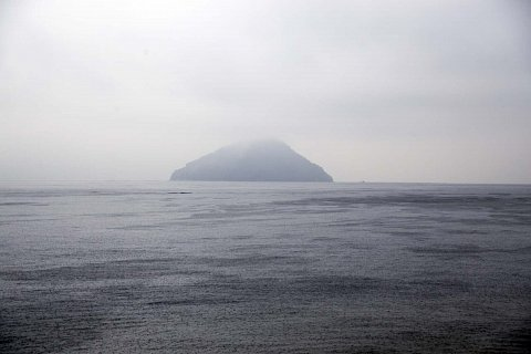 Island off Hiroshima in the rain. by Scott Joyce